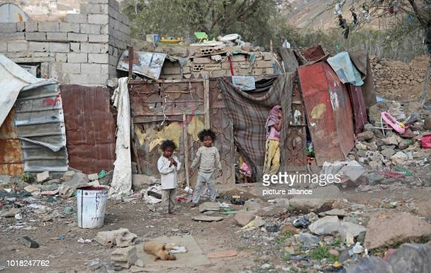 Yemeni children who were displaced from the coastal city of Al Hudaydah stand in front of a shelter where they live with their family in Sanaa Yemen...
