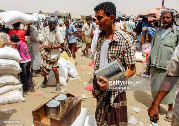 Yemeni civilians receive food aid for displaced people who fled battles in the Red Sea province of Hodeida and are now living in camps in the...