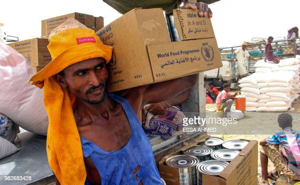 TOPSHOT Yemeni civilians receive food aid for displaced people who fled battles in the Red Sea province of Hodeida and are now living in camps in the...