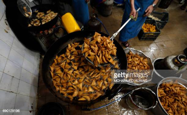 A Yemeni cook fries samosas at a shop in the capital Sanaa on May 30 2017 during the Muslim holy fasting month of Ramadan / AFP PHOTO / Mohammed...