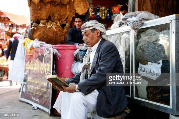A Yemeni craftsman reads a book outside his shop in the capital Sanaa's old city on March 1 2017 / AFP / Mohammed HUWAIS