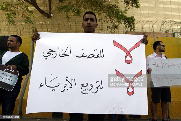 A Yemeni demonstrator carries a placard infront of the concrete barriers of the Saudi embassy in Sanaa on April 11 2015 during a gathering denouncing...