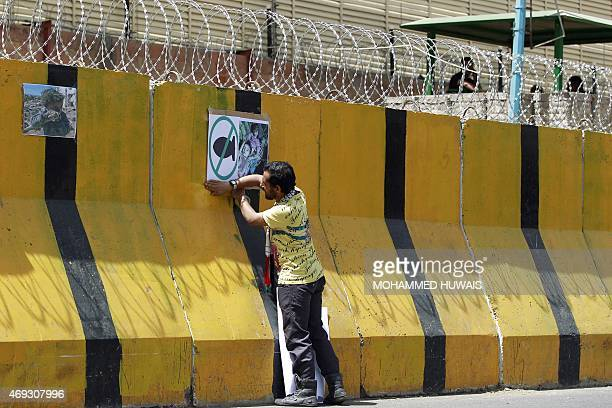 A Yemeni demonstrator places placards on the concrete barriers of the Saudi embassy in Sanaa on April 11 2015 during a gathering denouncing the...