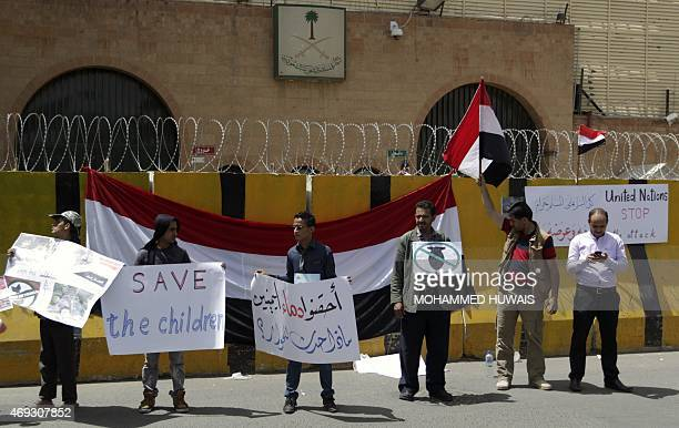 Yemeni demonstrators stand with placards in hand infront of a national flag placed on the concrete barriers of the Saudi embassy in Sanaa on April 11...