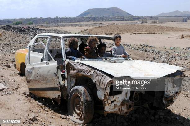 Yemeni displaced children who with their families fled homes due to the ongoing war enjoy riding a damaged car outside their makeshift shelter at an...