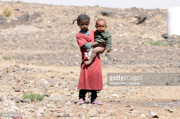 A Yemeni displaced girl who fled with her family their home due to the ongoing war carries her little brother outside their makeshift shelter at an...