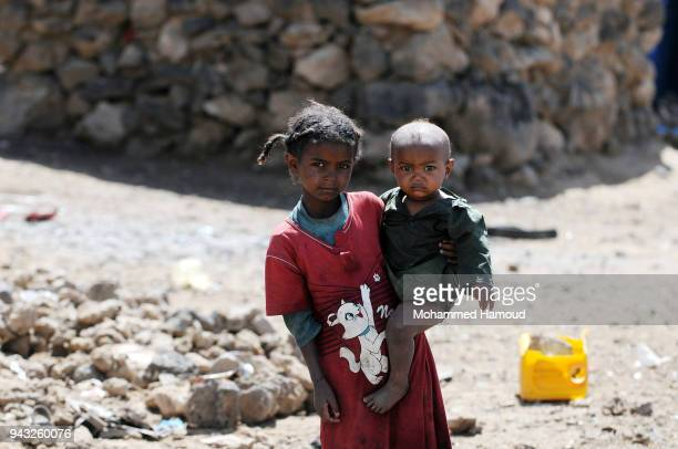 A Yemeni displaced girl who with her family fled home due to the ongoing war carries her little brother outside their makeshift shelter at an...