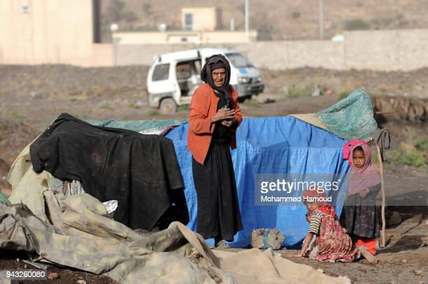 A Yemeni elderly displaced woman stands by her daughter's children outside their makeshift shelter at an internally displaced camp on April 07 2018...