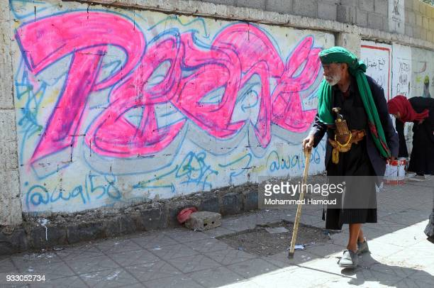 Yemeni elderly man wears ttaditional clotges walks by graffiti drew during an Open Day of graffiti campaign call for peace on March 15, 2018 in...