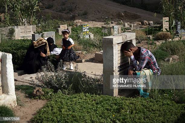 A Yemeni family pray near the graves of relatives on the first day of Eid alFitr in Sanaa on August 19 2012 Muslims in Yemen and some parts of the...