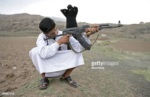 Yemeni family trains with an AK47 assault rifle on the outskirts of Sana'a Yemen on Friday April 28 2006 There are about 60 million firearms in the...