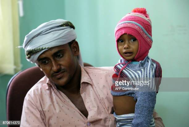 A Yemeni father carries his child suspected of being infected with cholera as he waits to be seen at a hospital in the Yemeni coastal city of...