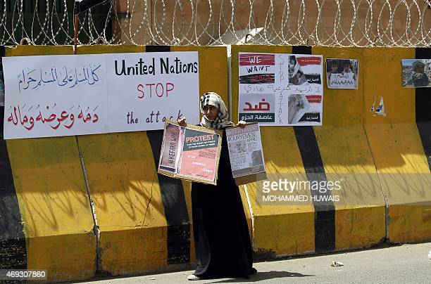 A Yemeni female demonstrator stands with placards in hand infront of concrete barriers of the Saudi embassy in Sanaa on April 11 2015 during a...