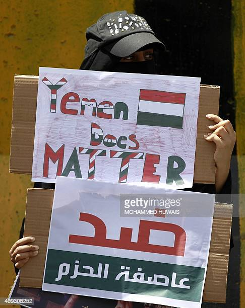 A Yemeni female demonstrator stands with placards in hand infront of the concrete barriers of the Saudi embassy in Sanaa on April 11 2015 during a...