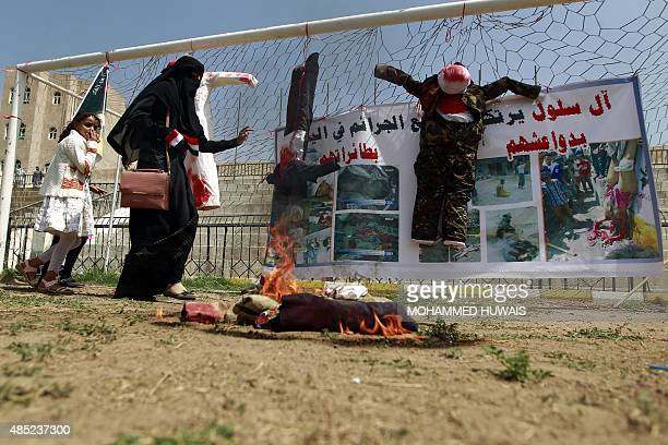 Yemeni female supporters of the Shiite Huthi rebel movement chant slogans as they stand next to a mockup depicting the victims of torture during a...