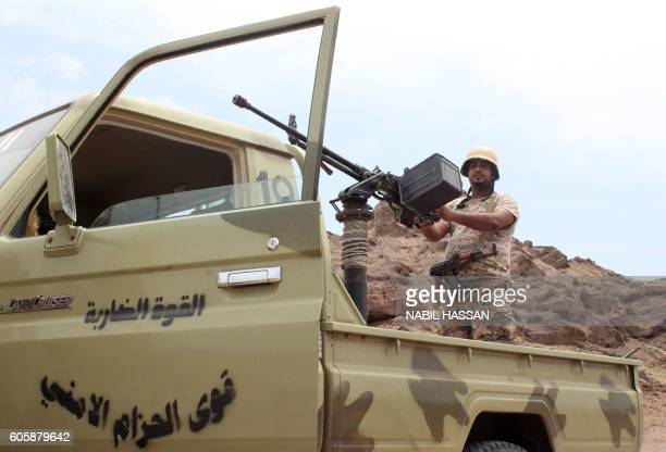 A Yemeni fighter loyal to President Abedrabbo Mansour Hadi stands on an armed pick up truck near Kahbub on a mountainous area overlooking the...