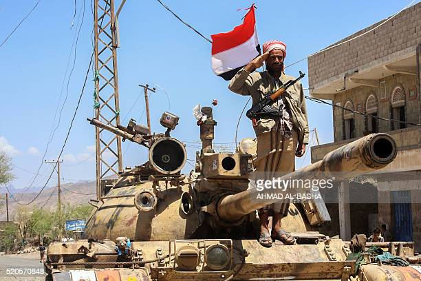 A Yemeni fighter loyal to the country's exiled president salutes on top of a tank at a checkpoint on a road in the southwestern city of Taez on April...