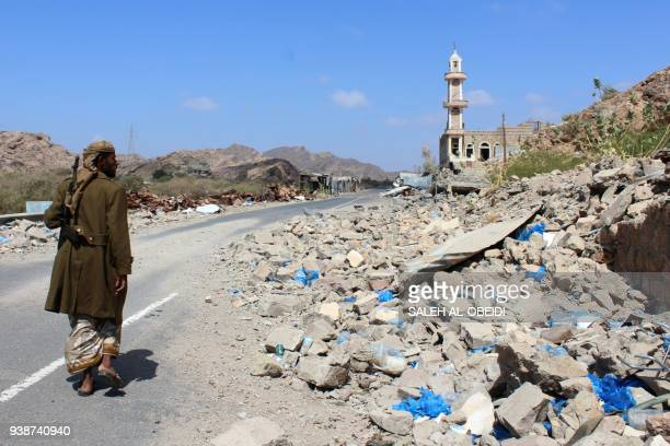Yemeni fighter loyal to the government backed by the Saudiled coalition walks past debris along a road near the town of AlShurayja in the southern...