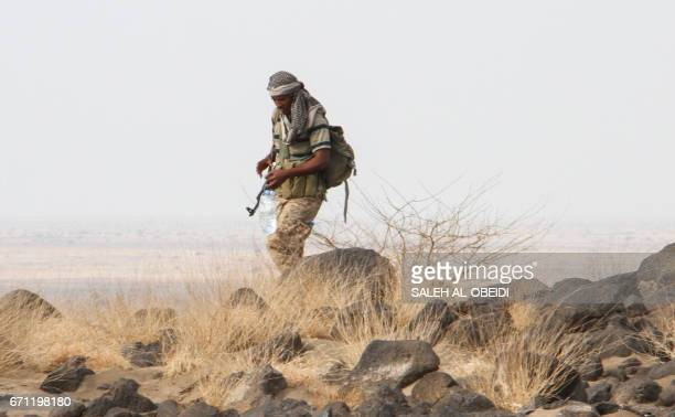 A Yemeni fighter loyal to the Saudibacked Yemeni president carries a bottle of water during a patrol of a hilltop position northwest of the central...