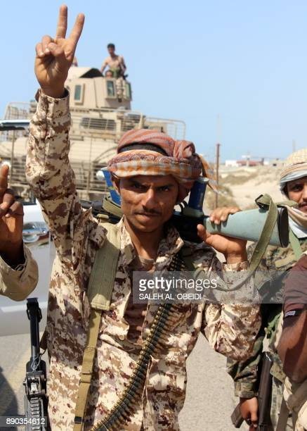 A Yemeni fighter loyal to the Saudibacked Yemeni president flashes the victory gesture as he walks on a road leading to the town of Khokha which was...