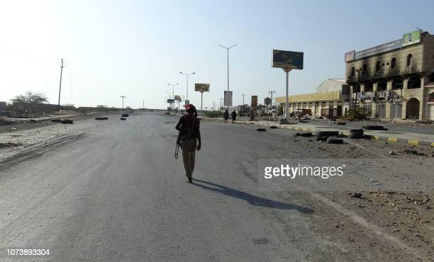 Yemeni fighter of the progovernment forces walks with a rifle in the Huthiheld Red Sea port city of Hodeida on December 15 2018 Residents of Yemen's...