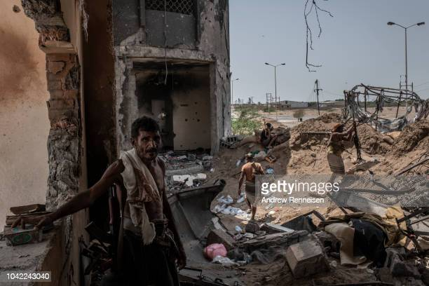 Yemeni fighters aligned with Yemen's Saudiled coalitionbacked government man a frontline position at Kilo 16 an area which contains the main supply...