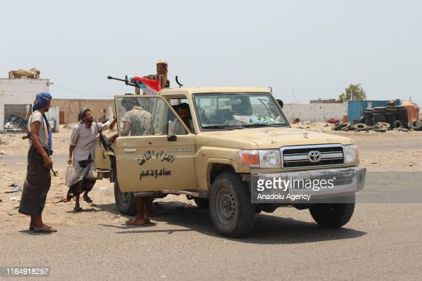 Yemeni fighters inspect burnt out vehicles as they take under control the site reportedly belonging to progovernment troops following yesterday's air...