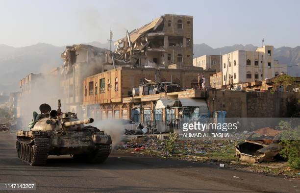 Yemeni fighters loyal to the country's exiled President Abedrabbo Mansour Hadi ride a tank past a destroyed building during clashes with Shiite Huthi...