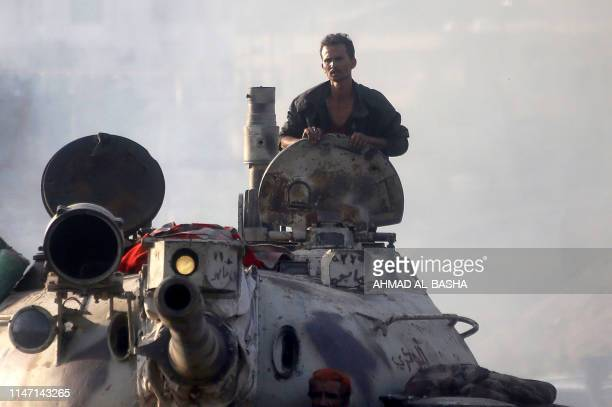 Yemeni fighters loyal to the country's exiled President Abedrabbo Mansour Hadi ride a tank during clashes with Shiite Huthi rebels in the country's...