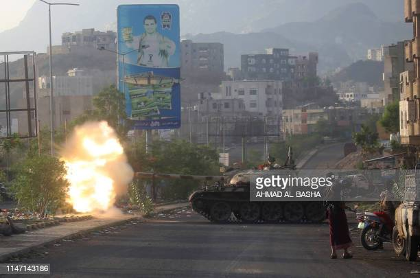 Yemeni fighters loyal to the country's exiled President Abedrabbo Mansour Hadi fire from a tank during clashes with Shiite Huthi rebels in the...