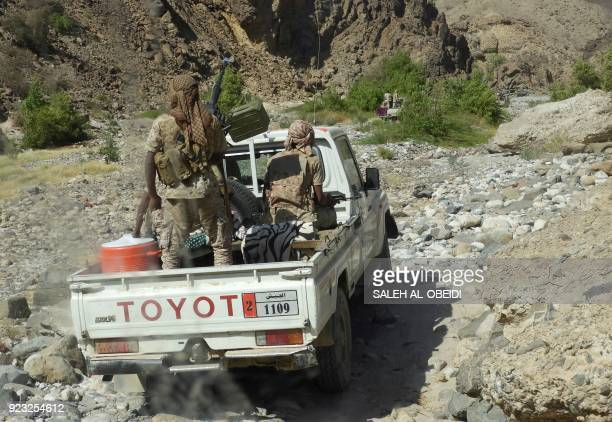 Yemeni fighters loyal to the government backed by the Saudiled coalition fighting in the country ride in the back of a pickup truck with mounted...
