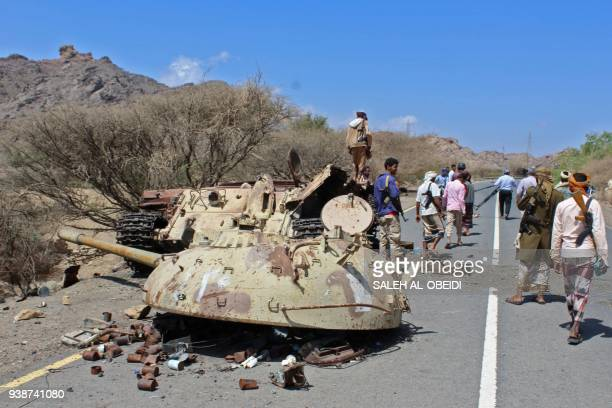 TOPSHOT Yemeni fighters loyal to the government backed by the Saudiled coalition gather around the destroyed turret and body of a tank near the town...
