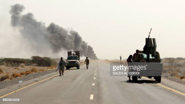 Yemeni fighters loyal to the Saudibacked Yemeni president are seen with their vehicles on the road leading to the town of Khokha which was retaken...