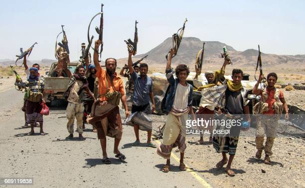 Yemeni fighters loyal to the Saudibacked Yemeni president pose for a picture raising their machine guns on April 15 on the road leading to Khaled Ibn...