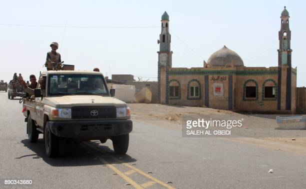 Yemeni fighters loyal to the Saudibacked Yemeni president ride in the back of a pickup truck past a mosque on a road leading to the town of Khokha...