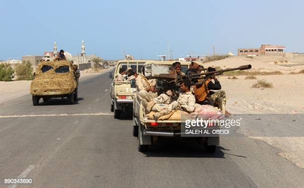 Yemeni fighters loyal to the Saudibacked Yemeni president ride in the back of a pickup truck as they man an antiaircraft gun on a road leading to the...