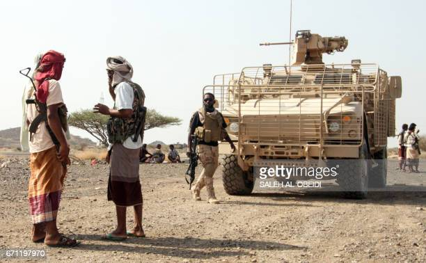Yemeni fighters loyal to the Saudi-backed Yemeni president stand by armoured vehicles at a position which was taken from Shiite-Huthi rebels in a...