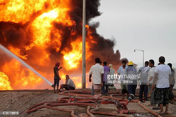Yemeni fighters of the southern separatist movement and firefighters attempt to extinguish a flame at an oil refinery in the port city of Aden on...