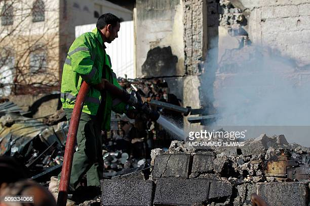 A Yemeni firefighter extinguishes smoke rising from buildings destroyed in an airstrike by the Saudiled coalition on February 10 2016 in the capital...