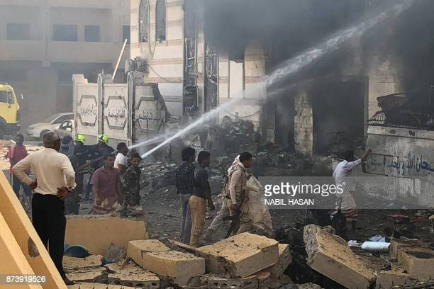Yemeni firefighters douse flames following an explosion near a security post in the southern port city of Aden on November 14 2017 / AFP PHOTO /...