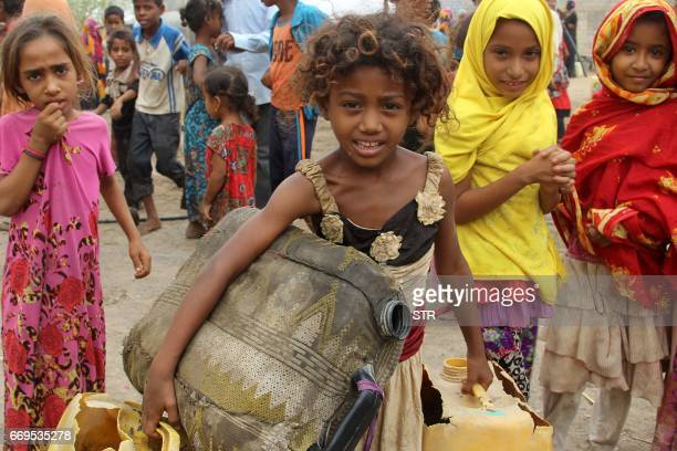 A Yemeni girl carries plastic containers as she heads to collect donated water from a truck in an impoverished coastal village on the outskirts of...