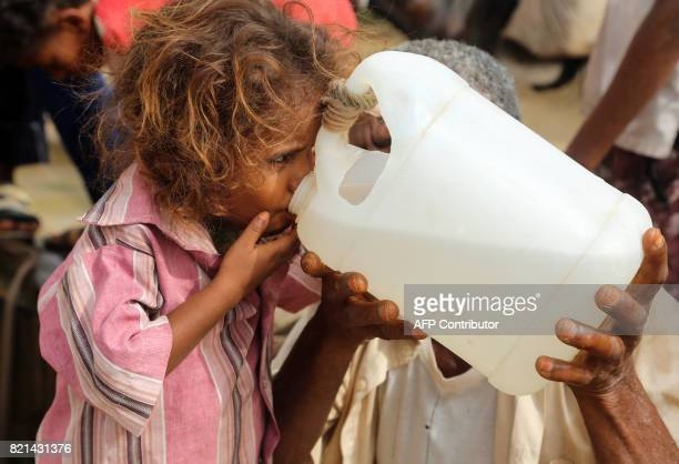 A Yemeni girl drinks water collected from a well in an impoverished village on the outskirts of the port city of Hodeidah on July 23 as the region...