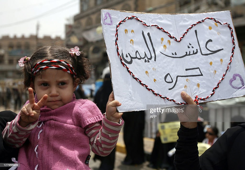 A Yemeni girl helps hold up a sign that reads in Arabic,