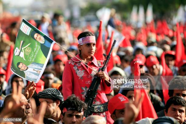 A Yemeni girl holds up a Kalashnikov assault rifle and waves a flag bearing the portraits of Shiite Huthi rebel leader Abdulmalik alHuthi and...
