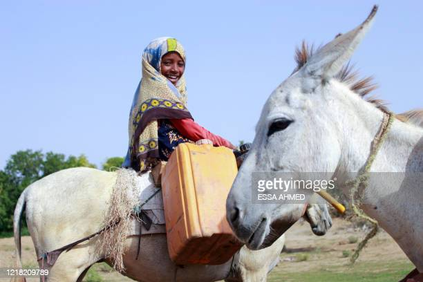 Yemeni girl riding a donkey waits to fill jerrycans with water from a cistern at a make-shift camp for the internally displaced, in the northern...