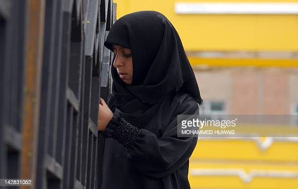 A Yemeni girl stands close by as antigovernment protesters perform the weekly Friday prayers during a rally in the capital Sanaa on April 13 2012...