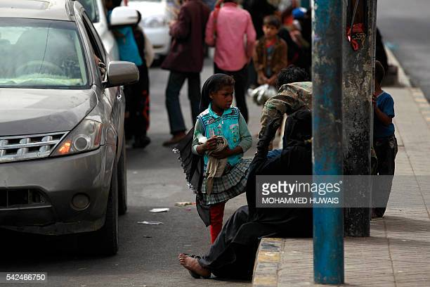 A Yemeni girl stands on the street as she waits to wash car windscreens in the capital Sanaa on June 23 2016 Yemen is regarded as one of the poorest...