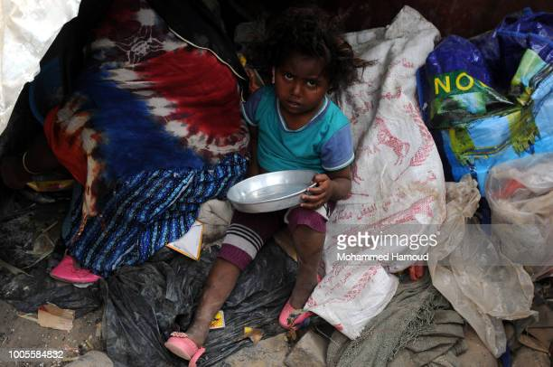 Yemeni girl who is displaced from Hodeidah holds an empty dish as she waits by her mother to be given some dough as a breakfast on July 22 2018 in...