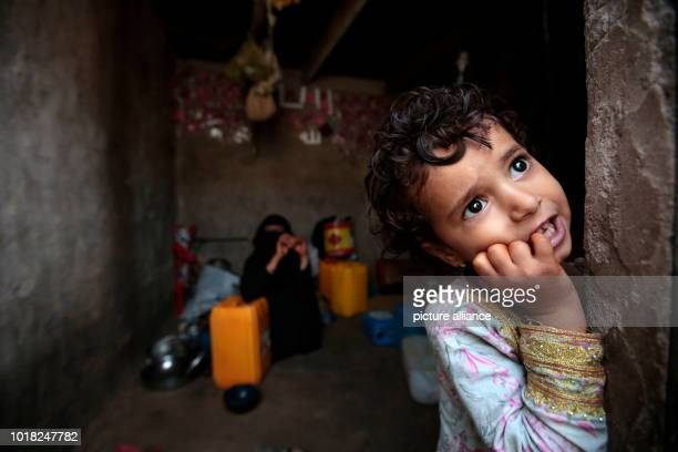 A Yemeni girl who was displaced from the coastal city of Al Hudaydah stands at the door of a shelter where she lives with her family in Sanaa Yemen...