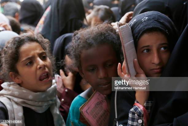 Yemeni girls, from families who were affected by the war and blockade, flock to receive free lunch meals, provided by a charitable kitchen at Mseek...